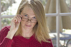 Blonde Frau-sitzendes Schauen über Spitze von Augen-Gläsern Lizenzfreie Stockfotos
