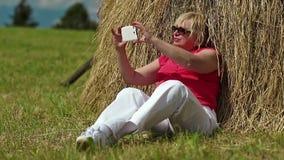 Blonde Frau sitzt auf grünem Gras nahe Heuschober und macht Fotos auf seinem Smartphone stock video footage