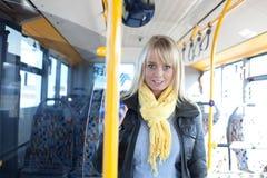 Blonde Frau steht innerhalb eines Busses Stockfotografie