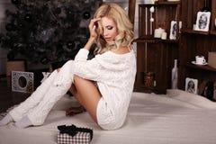 Blonde Frau trägt die gemütliche gestrickte Wolljacke und wirft neben Weihnachtsbaum auf Stockbild