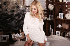 Blonde Frau trägt die gemütliche gestrickte Wolljacke und wirft neben Weihnachtsbaum auf Lizenzfreie Stockfotos