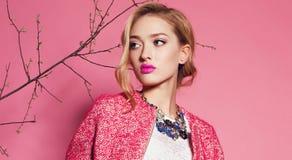 Blonde Frau trägt eleganten rosa Mantel, Bluse und luxuriöse Halskette Stockfotos