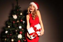 Blonde Frau trägt Sankt-Hut, der mit Geschenken, neben Weihnachtsbaum aufwirft Stockbilder