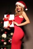 Blonde Frau trägt Sankt-Hut, der mit Geschenken, neben Weihnachtsbaum aufwirft Stockfotos