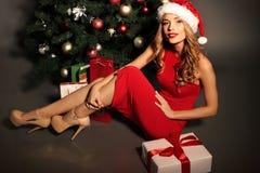 Blonde Frau trägt Sankt-Hut, der mit Geschenken, neben Weihnachtsbaum aufwirft Lizenzfreies Stockfoto
