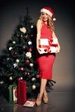 Blonde Frau trägt Sankt-Hut, der mit Geschenken, neben Weihnachtsbaum aufwirft Lizenzfreie Stockbilder
