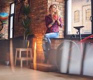 Blonde Frau trinkt heißen Kaffee nahe dem Fenster Lizenzfreie Stockbilder