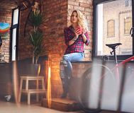 Blonde Frau trinkt heißen Kaffee nahe dem Fenster Stockfotos