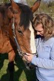 Blonde Frau umarmt ihr Pferd lizenzfreie stockbilder