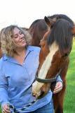 Blonde Frau umarmt ihr Pferd stockfotos