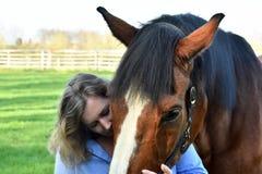 Blonde Frau umarmt ihr Pferd lizenzfreies stockbild