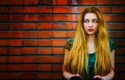 Blonde Frau und Backsteinmauer stockbild