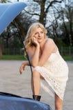 Blonde Frau und beschädigtes Fahrzeug Stockfotografie