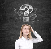 Blonde Frau und ein großes Fragezeichen auf Tafel Lizenzfreies Stockbild