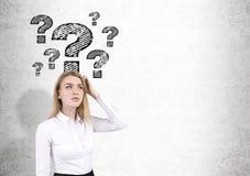 Blonde Frau und Fragezeichen auf Betonmauer Lizenzfreies Stockfoto