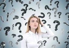 Blonde Frau und Fragezeichen auf grauer Wand Lizenzfreie Stockbilder