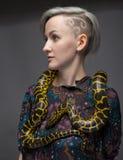 Blonde Frau und gelbes Reptil Stockbilder