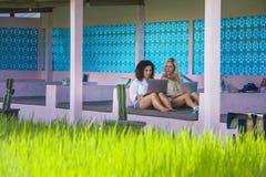 Blonde Frau und lateinisches Mischmädchen, die online draußen zusammen mit Laptop-Computer vor Reisfeld als digitaler Nomade Frei Stockbild