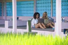 Blonde Frau und lateinisches Mischmädchen, die online draußen zusammen mit Laptop-Computer vor Reisfeld als digitaler Nomade Frei Lizenzfreie Stockfotografie