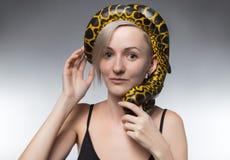 Blonde Frau und Schlange auf ihrem Kopf Lizenzfreies Stockbild