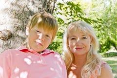 Blonde Frau und Sohn, die im Sommer lächelt Lizenzfreies Stockfoto