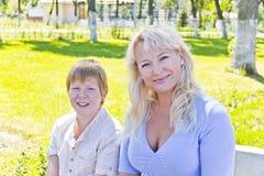 Blonde Frau und Sohn, die im Sommer lächelt Stockfotos