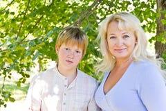 Blonde Frau und Sohn, die im Sommer lächelt Stockfoto