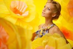 Blonde Frau unter großen gelben Blumen Lizenzfreie Stockbilder