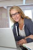 Blonde Frau von mittlerem Alter auf Laptop Lizenzfreie Stockfotos