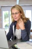 Blonde Frau von mittlerem Alter, die an Computer arbeitet Stockfotos