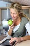Blonde Frau von mittlerem Alter, die grünen Apfel isst Stockfotografie