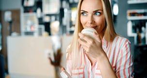Blonde Frau von mittlerem Alter, die Kosmetik setzt stockfotografie