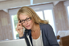Blonde Frau von mittlerem Alter, die an Laptop arbeitet Stockfoto