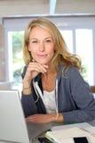 Blonde Frau von mittlerem Alter, die an Laptop arbeitet Lizenzfreies Stockfoto