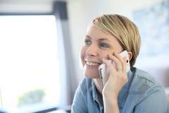 Blonde Frau von mittlerem Alter, die am Telefon spricht Lizenzfreie Stockbilder