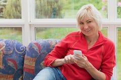 Blonde Frau von mittlerem Alter hält einen Handy Stockbilder