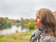 Blonde Frau von mittlerem Alter im Herbst auf dem Hintergrund der Natur Lizenzfreies Stockfoto