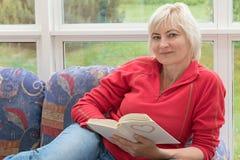 Blonde Frau von mittlerem Alter ist mit einem Buch in ihren Händen entspannend Lizenzfreie Stockbilder