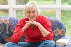 Blonde Frau von mittlerem Alter lächelt zur Kamera Lizenzfreie Stockfotos