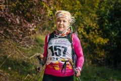 Blonde Frau von mittlerem Alter läuft durch Herbstwald mit nordischen Wanderstöcken Stockfotos