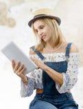 Blonde Frau von mittlerem Alter mit Tablette Stockbild