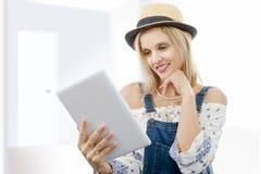 Blonde Frau von mittlerem Alter mit Tablette Stockfoto