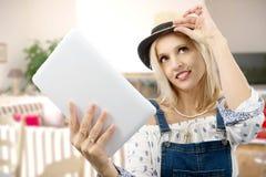 Blonde Frau von mittlerem Alter mit Tablette Stockfotos
