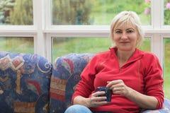 Blonde Frau von mittlerem Alter sitzt auf einem Sofa Stockbild