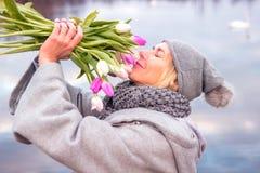 Blonde Frau vor See mit Tulpen Stockfotografie