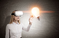 Blonde Frau in vr Gläsern nahe einer Tafel mit einer Glühlampe Lizenzfreie Stockfotos