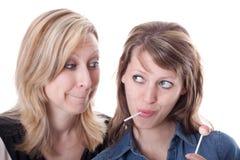 Blonde Frau wünscht Lutschbonbon von der Brunettefrau Stockfotografie