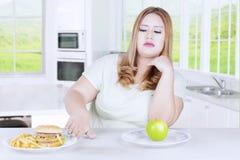 Blonde Frau weist Burger in der Küche zurück Stockfotografie