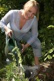 Blonde Frau, welche die Anlagen wässert stockfotos