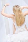 Blonde Frau, welche die Borduhr ausdehnt und betrachtet Lizenzfreies Stockfoto
